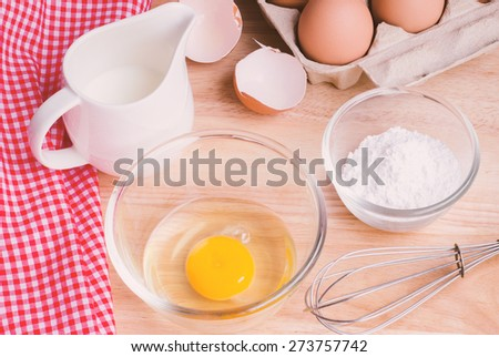 Cookies ingredients. Bowl, flour, eggs, jar of milk, eggbeater,eggshells and red napkin - stock photo