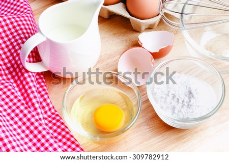 Cookies ingredients.Bowl, flour, eggs, jar of milk, eggbeater,eggshells and red napkin - stock photo