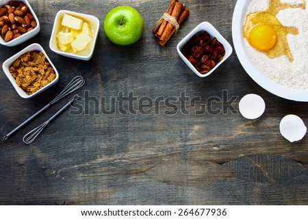 Cookies ingredients (raw egg, brown sugar, apple, butter and flour) over rustic wood with copyspace. Top view. Food and cuisine background. - stock photo