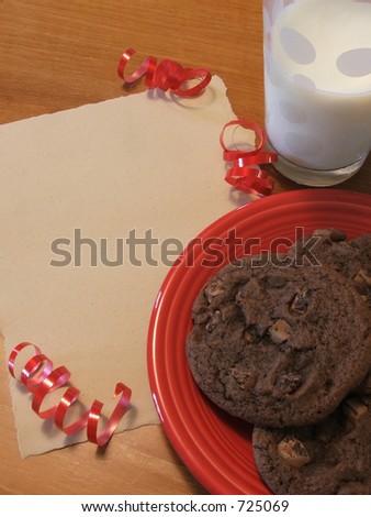 Cookies & milk wait for Santa next to a blank wishlist. - stock photo