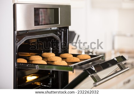 Cookies on the grid in the oven. - stock photo