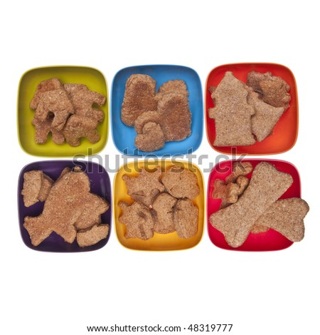 Cookies or pet treats in various shapes displayed in vibrant bowls over white.  File includes a clipping path. - stock photo