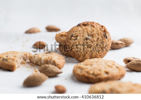 Cookies pile with chocolate chip and almond on light textile background. Delicious morning snacks for breakfast, brunch and lunch. Appetizing, healthy and fast food