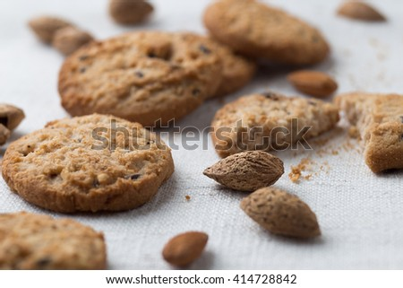 Cookies pile with chocolate chip and almond on light textile background. Delicious morning snacks for breakfast, brunch and lunch. Appetizing, healthy and fast food - stock photo