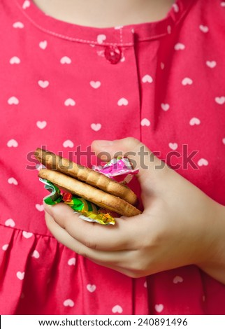 Cookies with candy, trapped in a child's hand at the breast - stock photo