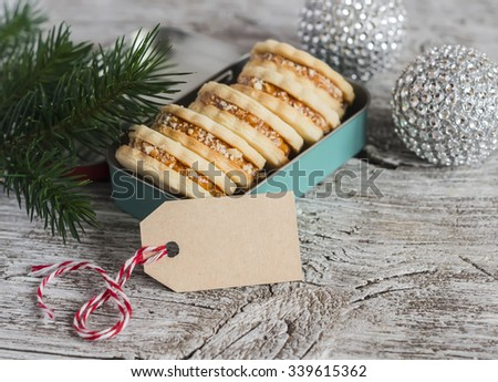 Cookies with caramel cream and walnuts in a vintage metal box, Christmas decoration and a clean, empty tag on bright wooden surface. Free space for text
