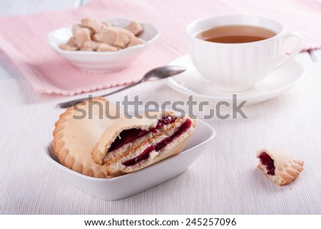 Cookies with cherry jam, cup of tea, sugar. Teatime.  - stock photo