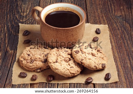 Cookies with chocolate and cup of black coffee on old wooden table - stock photo