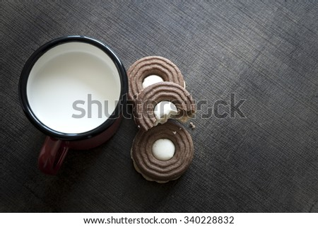 Cookies with chocolate cream on a wooden table - stock photo
