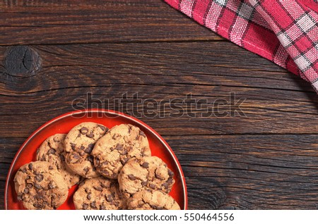 Cookies with chocolate in red plate on dark wooden table, top view