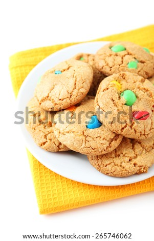 Cookies with colorful candy on plate on white background - stock photo