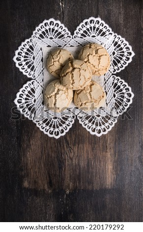Cookies with cracks on  laced napkin  dark old desk , top view background with copy space - stock photo