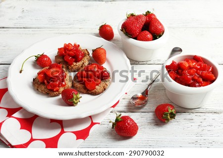 Cookies with fresh strawberry in plate on wooden table, closeup