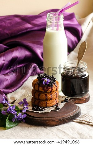 Cookies with jam, bottle of milk and flowers of violets on the table - stock photo