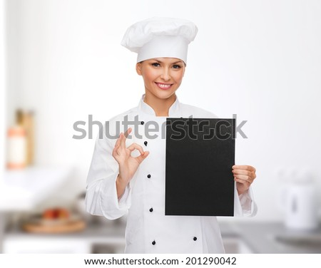 cooking, advertisement and food concept - smiling female chef, cook or baker with blank black paper showing ok sing - stock photo
