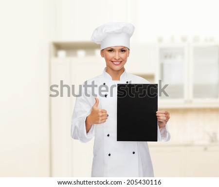 cooking, advertisement and food concept - smiling female chef, cook or baker with blank black paper showing thumbs up - stock photo