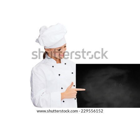 cooking, advertisement and people concept - smiling female chef, cook or baker pointing finger to blank blackboard over white background - stock photo