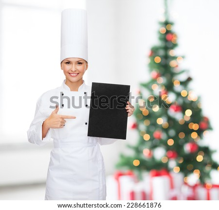 cooking, advertisement, holidays and people concept - smiling female chef, cook or baker pointing finger to blank black menu paper over living room and christmas tree background - stock photo