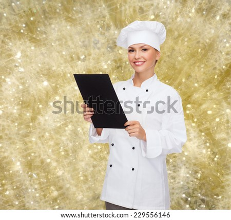 cooking, advertisement, holidays and people concept - smiling female chef, cook or baker with blank black menu paper over yellow lights background - stock photo