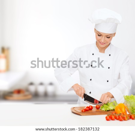 cooking and food concept - smiling female chef, cook or baker chopping vegetables - stock photo