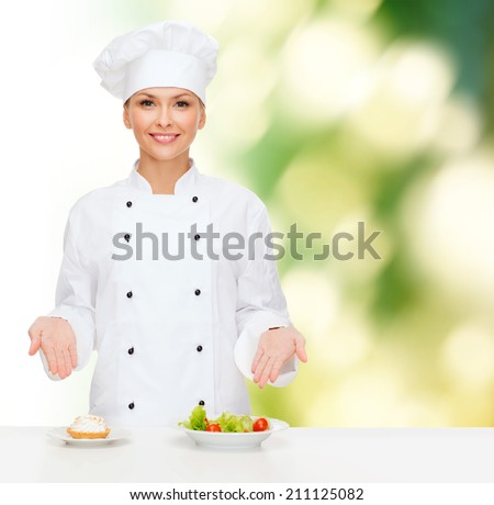 cooking and food concept - smiling female chef, cook or baker with salad and cake on plates - stock photo