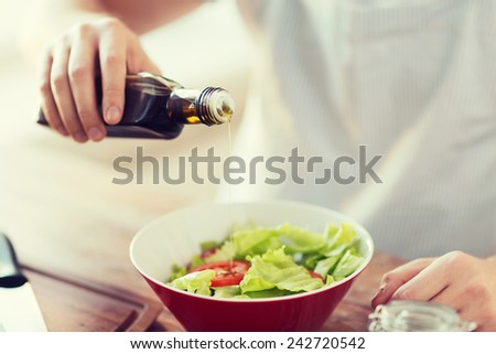 cooking and home concept - close up of male hands flavouring salad in a bowl with olive oil - stock photo
