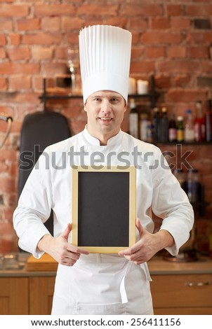 cooking and people concept - happy male chef cook with black blank menu chalk board in kitchen in restaurant kitchen - stock photo