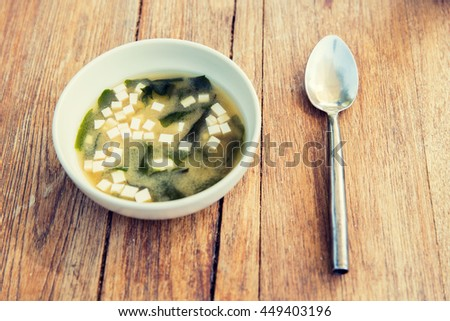cooking, asian kitchen and food concept - bowl of soup with tofu cheese and spoon on wooden table - stock photo