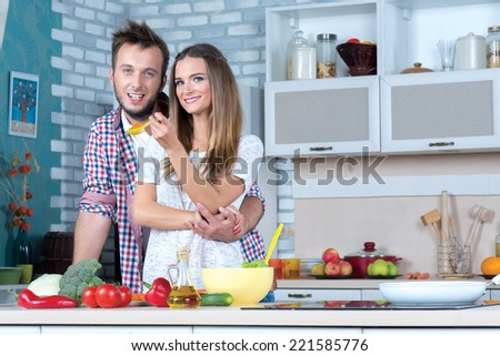Cooking at home. Young and beautiful couple in love is staying in the kitchen and cooking dinner for romantic evening - stock photo