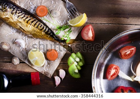 Cooking background. Smoked fish with spices,fruits and lemon on a wooden background. - stock photo