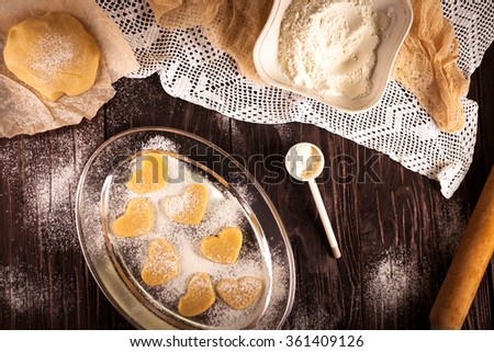 cooking biscuits in the shape of a heart on a wooden brown background, flour, rolling pin, the concept of Valentine's Day - stock photo