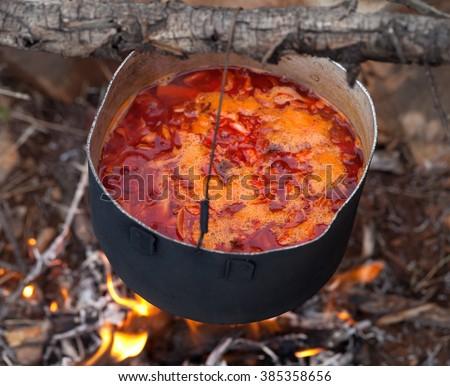 Cooking borscht (Ukrainian traditional soup) on campfire. Close-up view. - stock photo