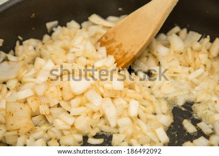 Cooking chopped onions in hot oil in a frying pan - stock photo