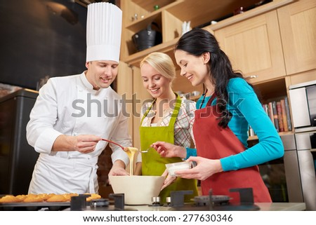 cooking class, culinary, bakery, food and people concept - happy group of women and male chef cook baking muffins in kitchen - stock photo