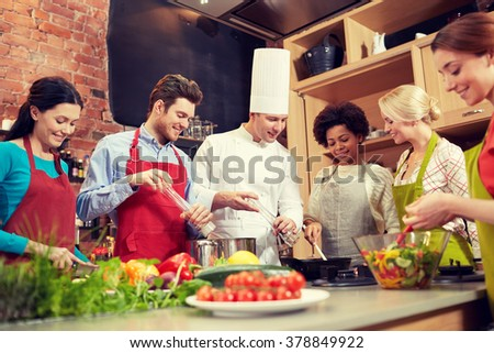 cooking class, culinary, food and people concept - happy group of friends and male chef cook cooking in kitchen - stock photo