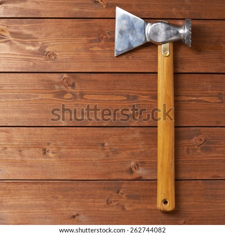 Cooking composition of the rustic meat tenderizer over the wooden table's surface - stock photo