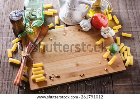 Cooking concept. Chopping board with copyspace and ingredients for cooking pasta over rustic wooden background. Selective focus; the front view of the image is out of focus and has shallow DoF - stock photo