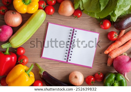 Cooking concept. Empty Recipe book surrounded of colorful fresh vegetables over wooden background. Top view - stock photo