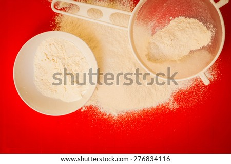 Cooking concept. Preparation for baking, bake ingredients and kitchen tools to make a cake, sifting wheat flour on red nonstick silicone mat, top view - stock photo