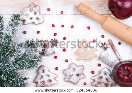 Cooking cookies. Flour, chocolate, cranberries, apples, spices, rolling pin on a wooden background. Christmas background. Top view - stock photo