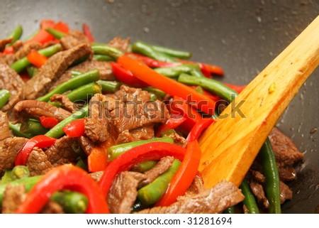 Cooking delicious beef, bean, capsicum stir-fry - stock photo