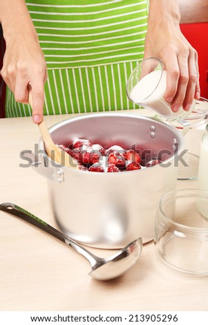 Cooking delicious strawberry jam in kitchen - stock photo