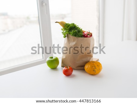 cooking, diet, vegetarian food and healthy eating concept - close up of paper bag with fresh ripe juicy vegetables, greens and fruits on kitchen table at home - stock photo