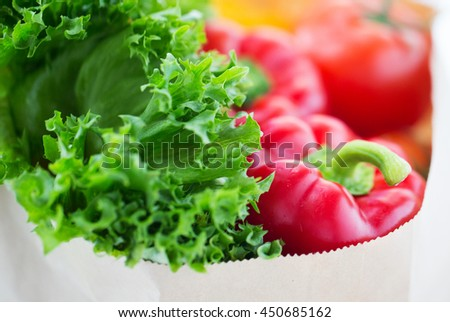 cooking, diet, vegetarian food and healthy eating concept - close up of paper bag with fresh ripe juicy vegetables and greens on kitchen table at home - stock photo