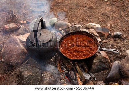 Cooking Dinner on campfire in cast iron pan. - stock photo