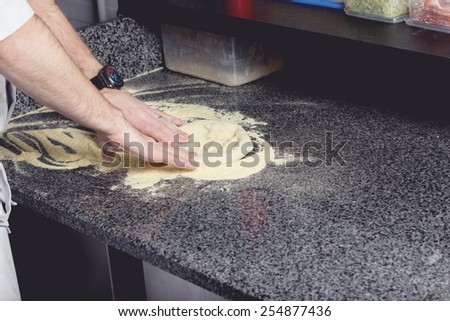 cooking dough pizza on granite counter top - stock photo