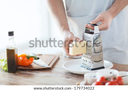 cooking, food and home concept - close up of male hands grating cheese - stock photo