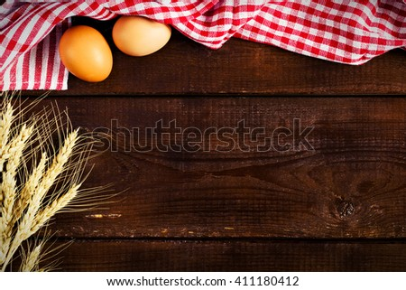 Cooking food background / Wooden background with plaid kitchen towel, fresh chicken eggs and golden wheat ears. Copy space for text - stock photo