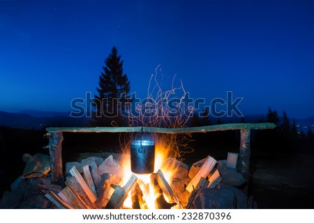 Cooking food in the pot on fire under blue night sky with many stars - stock photo