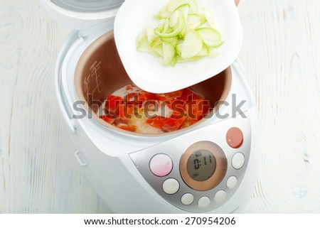 cooking fried salmon with leek in multicooker closeup - stock photo